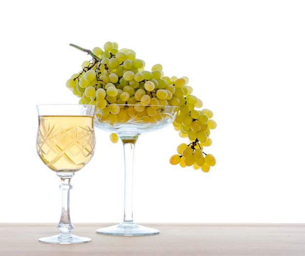 Vinho em um copo com uvas, isolado em um fundo branco.