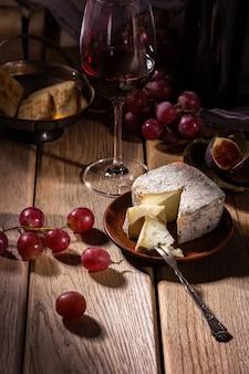 Vinho, figos, uvas e um copo em uma mesa de madeira