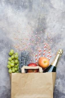 Vinho, frutas, flores (conjunto para a festa ou piquenique) em um pacote de ofício de papel sobre um fundo cinza concreto. vista do topo.