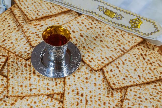 Vinho kosher vermelho com uma placa branca do matzah ou do matza e um hagadá do passover em um fundo de madeira do vintage apresentado como uma refeição do seder da páscoa judaica com espaço da cópia.