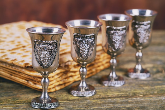 Vinho kosher vermelho quatro de matzah ou matza páscoa hagadá sobre um fundo de madeira vintage
