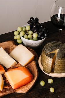 Vinho perto de uvas e queijo