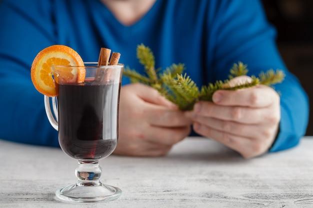 Vinho quente com adição de laranja, mel, canela, cravo e anis, as mãos do homem seguram com vinho quente