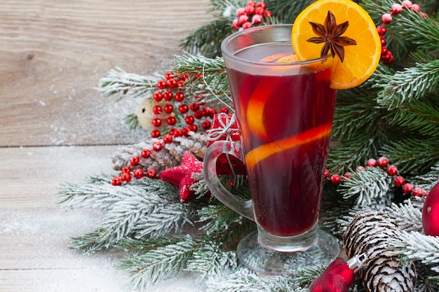 Vinho quente com árvore de natal decorada na neve