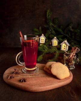 Vinho quente com biscoitos de gengibre, anis estrelado, canela. fundo escuro com galhos de pinheiro e luzes luminosas