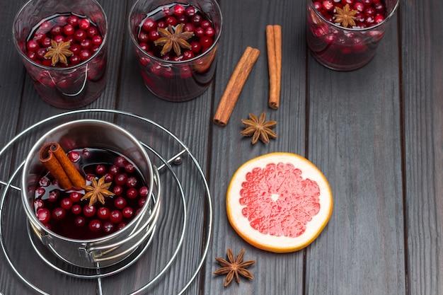 Vinho quente com cranberries e especiarias. anis estrelado e fatia de toranja na mesa