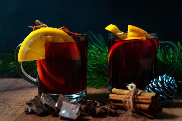 Vinho quente com especiarias aromáticas e pedaços de laranja em fundo de madeira
