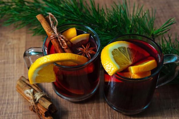 Vinho quente com especiarias aromáticas em fundo de madeira