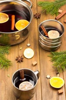 Vinho quente com especiarias com especiarias em canecas de metal e panela. anis estrelado, fatias de laranja e paus de canela na mesa.