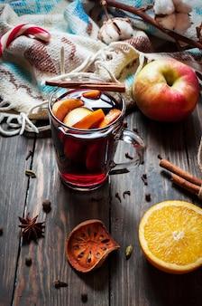 Vinho quente com especiarias com especiarias, maçã e laranja em fundo de madeira
