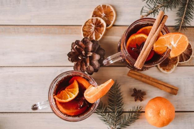 Vinho quente com especiarias com frutas e especiarias em um fundo de madeira bebida para o aquecimento do inverno para as férias