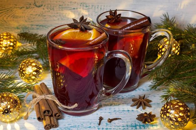 Vinho quente com especiarias com laranja, anis e canela no fundo de galhos de árvores de natal e festão. bebida de natal de aquecimento.