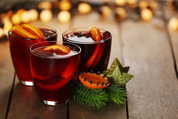 Vinho quente com especiarias e árvore de natal com fundo de madeira