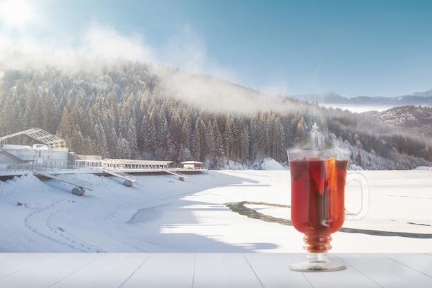 Vinho quente com especiarias e paisagem de montanhas no fundo. bebida quente de álcool na frente de montanhas nevadas e céu nublado. quente no dia de inverno, feriados, viagens, ano novo e época do natal. .