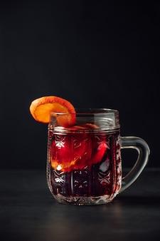 Vinho quente com especiarias em copo de vidro em um fundo escuro. bebida quente de natal com especiarias e frutas.