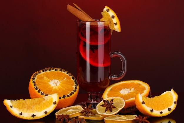Vinho quente com especiarias em um copo com especiarias e laranjas em torno de um fundo vermelho
