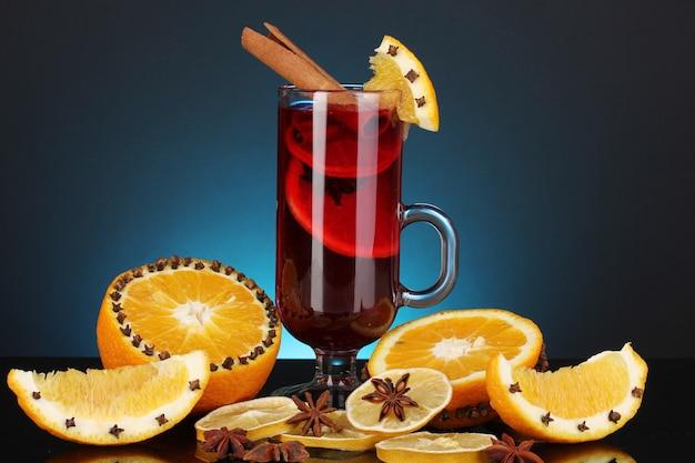 Vinho quente com especiarias em um copo com especiarias e laranjas em um fundo azul
