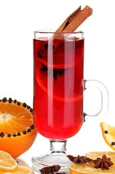 Vinho quente com especiarias em um copo com especiarias e laranjas isoladas em branco