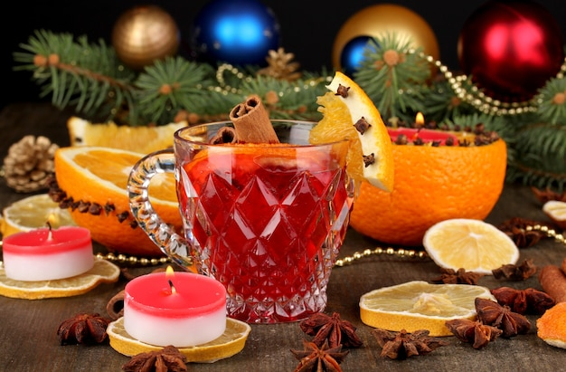 Vinho quente com especiarias em um copo com especiarias e laranjas na mesa de madeira