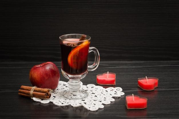 Vinho quente com especiarias em um guardanapo de renda. velas em forma de coração, paus de canela e maçã.