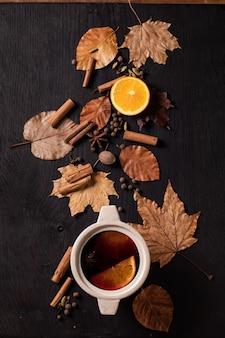 Vinho quente com especiarias em uma panela de cerâmica com especiarias, laranja e folhas de outono sobre fundo preto de madeira. postura plana. bebidas quentes aconchegantes
