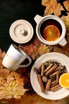 Vinho quente com especiarias em uma panela de cerâmica e caneca com especiarias, laranja e folhas de outono sobre fundo preto de madeira. postura plana. bebidas alcoólicas mornas e aconchegantes. top vew