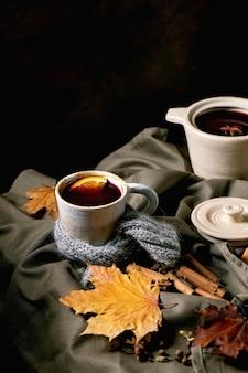 Vinho quente com especiarias em uma panela de cerâmica e caneca em lenço com especiarias, laranja e folhas de outono sobre toalha de mesa de linho escuro. bebidas alcoólicas mornas e aconchegantes. copie o espaço