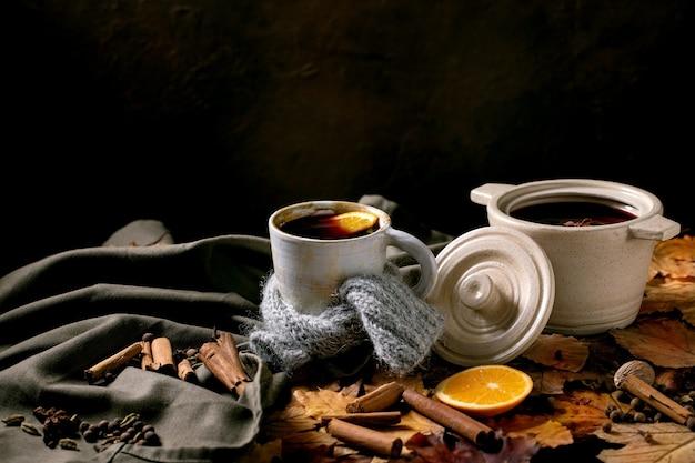 Vinho quente com especiarias em uma panela de cerâmica e caneca em lenço com especiarias, laranja e folhas de outono sobre toalha de mesa de linho escuro. copie o espaço. atmosfera acolhedora e calorosa