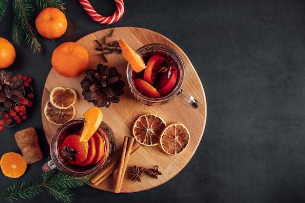 Vinho quente com especiarias em uma xícara de vidro. bebida quente de inverno com especiarias e frutas.