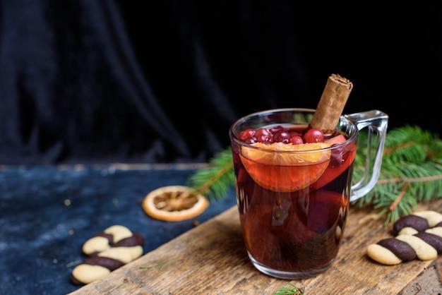 Vinho quente com especiarias para o inverno e o natal na mesa de madeira
