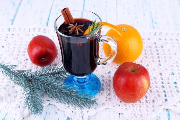 Vinho quente com especiarias tinto com frutas e galho de árvore de natal em guardanapo, fundo de superfície de madeira