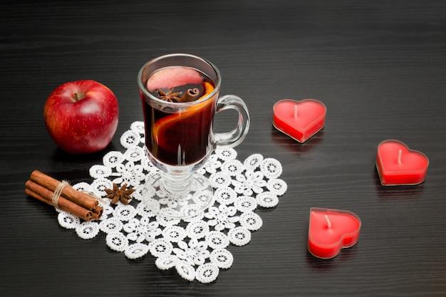Vinho quente com especiarias. velas em forma de coração, paus de canela e maçã. parede de madeira preta