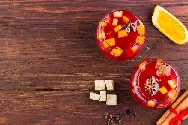 Vinho quente com frutas cítricas em vidro em madeira escura, vista superior, copie o espaço