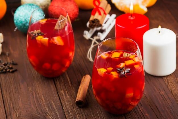 Vinho quente com frutas cítricas em vidro em madeira escura