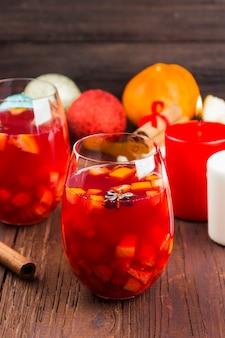 Vinho quente com frutas cítricas em vidro sobre uma superfície de madeira escura
