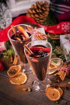 Vinho quente com frutas, paus de canela, anis, decorações e caixas de presente em fundo escuro de madeira. bebida de aquecimento do inverno com ingredientes da receita.