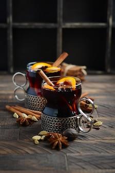 Vinho quente com laranjas e especiarias na mesa de madeira velha.