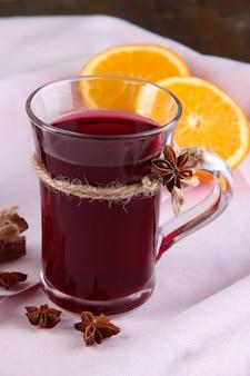 Vinho quente com laranjas na mesa de perto