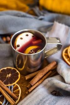 Vinho quente com maçã, laranja, cravo, canela e anis em uma caneca de metal