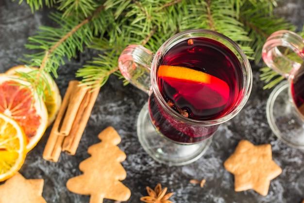 Vinho quente de natal com biscoitos de gengibre, laranja, canela, cravo, anis e, abeto na mesa preta