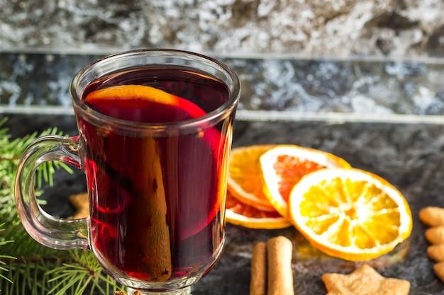 Vinho quente de natal com biscoitos de gengibre, laranja, canela, cravo-da-índia e pinheiro na mesa preta escura