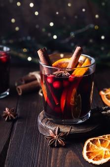 Vinho quente de natal com cranberries laranja e especiarias em fundo de madeira rústico