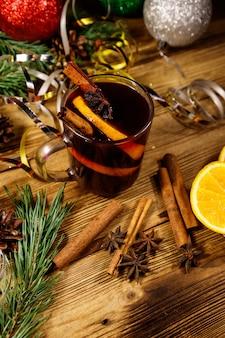 Vinho quente de natal com especiarias e decoração de natal na mesa de madeira