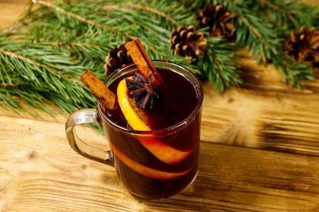 Vinho quente de natal com especiarias e galhos de árvores de abeto e cones na mesa de madeira