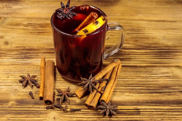 Vinho quente e especiarias na mesa de madeira