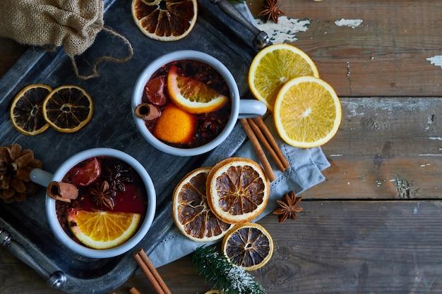 Vinho quente em canecas de metal cinza com laranja e especiarias estilo rústico