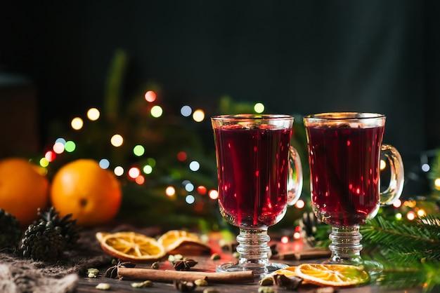 Vinho quente em copos em cima da mesa com decoração de natal
