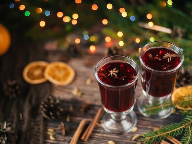 Vinho quente em copos em um fundo de madeira com especiarias e ingredientes com decoração de natal