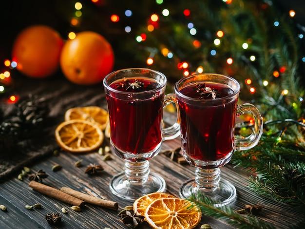 Vinho quente em copos na mesa decorada com uma árvore de natal. fatias de laranja, estrelas de anis, cardamomo, canela