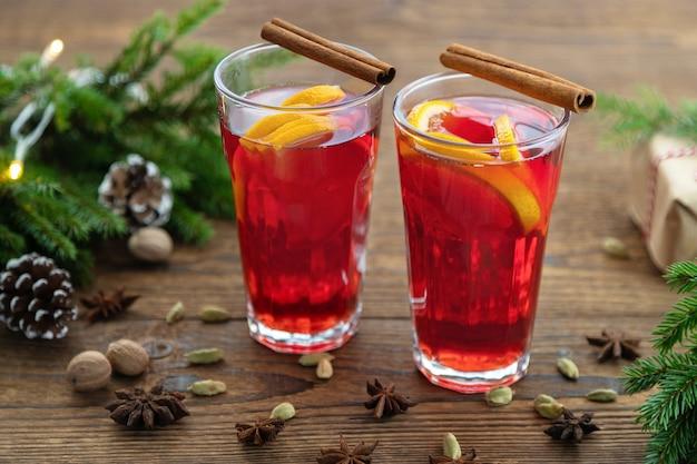 Vinho quente em taças de vidro decoradas com paus de canela em uma mesa de madeira; nas proximidades, há ramos de abeto verde e cones. bebida de natal, ponche de ano novo.